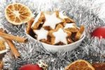 Thumbnail Cinnamon flavored star-shaped biscuits in white bowl, christmas decorations, cinnamon sticks, orange slices and christmas tree balls