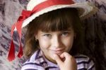 Thumbnail Girl wearing a hat with red ribbon