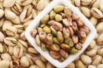 Thumbnail Pistachio nuts in a white bowl resting on pistachios
