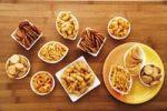 Thumbnail Various spiced snacks in bowls on a table, crisps, peanut flips, potato sticks, roasted peanuts, pretzel sticks and potato rings