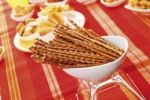Thumbnail Pretzel sticks in a white bowl with different spiced snacks