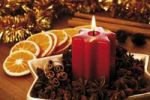 Thumbnail Lightened star-shaped candle on a christmas decoration platter with star anise, cinnamon sticks, dried orange slices, gold tinsel in the background