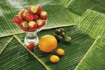Thumbnail Composition of fruits on bed of banana leaves, strawberries Fragaria, Oranges Citrus sinensis, Kumquats or Cumquats Fortunella and Kiwi fruit Actinidia chinensis originally known as Chinese Gooseb