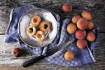 Thumbnail Fresh apricots on a tin plate, with a knife and kitchen towel on a wooden background