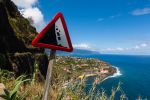 "Thumbnail Sign, """"Beware falling rocks"""" on a country road along the coastal cliffs near Ponta Delgada / Vicente, Ponta Delgada, Ilha da Madeira, Portugal, Europe"