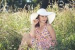 Thumbnail Young woman with a hat and a summer dress sitting in tall grass, outdoor portrait