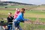 Thumbnail Mother and two daughters with bicycles in rural landscape