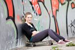 Thumbnail Teenage girl with skateboard in urban surroundings