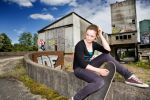 Thumbnail Portrait of a young teenage girl with a skateboard sitting in an urban area