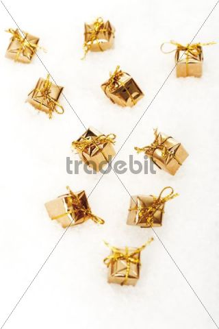 Presents in the snow wrapped in gold