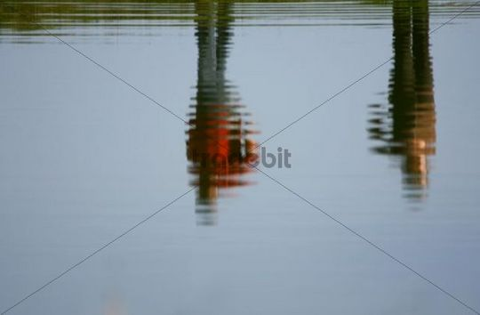 Two people reflected in a lake
