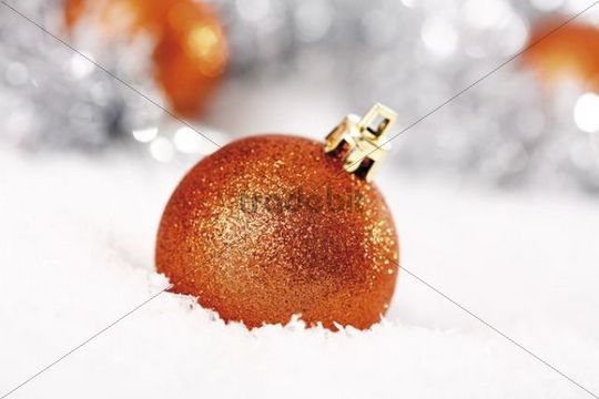 Orange glitter Christmas tree balls on snow with Christmas decorations