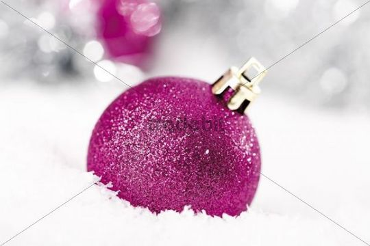 Pink glitter Christmas tree balls on snow with Christmas decorations