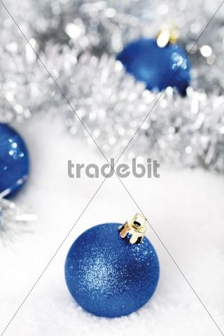 Blue glitter Christmas tree balls on snow with Christmas decorations