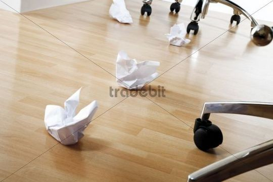 Crumpled-up paper on laminate flooring between office chairs