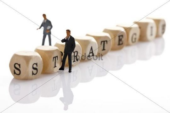 Strategie, German for strategy, written with wooden letters and two miniature manager figures