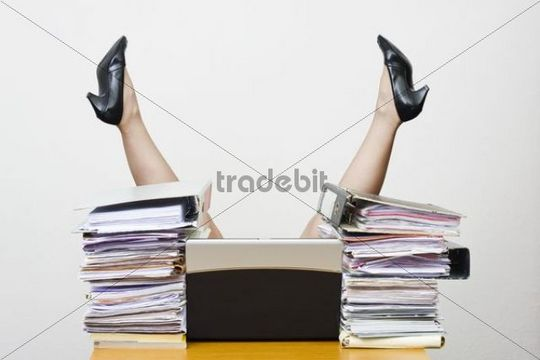 Legs of an overworked businesswoman sticking up in the air behind a desk loaded with files