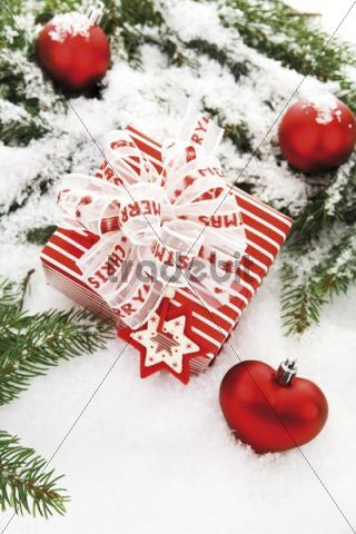 Christmas present with branches of fir, heart-shaped Christmas tree baubles and decorations on snow