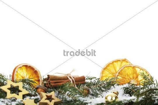 Dried slices of orange, sticks of cinnamon and christmas decoration on snow-covered pine branches