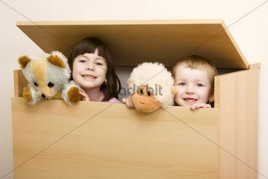 Two sisters, 6 and 3 years, hiding in a box