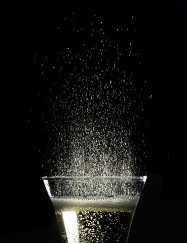 Champagne glass, fizzy champagne drops in light