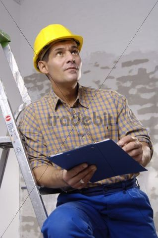 Workman wearing a hard hat leaning against a ladder, pensive