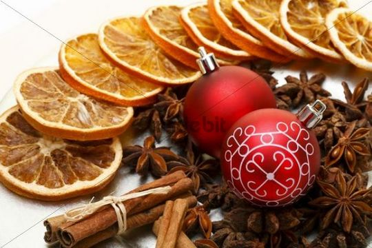 Christmas baubles, star anise, cinnamon sticks and dried slices of orange on a plate