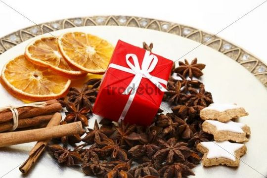 Christmas present, star anise, cinnamon sticks and dried slices of orange on a plate