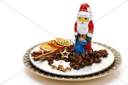 Chocolate Santa, star-shaped cinnamon cookies, star anise, cinnamon sticks and dried slices of orange on a plate