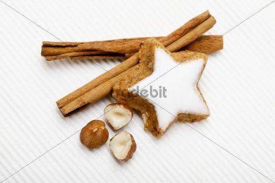 Star-shaped cinnamon cookie with cinnamon sticks and hazlenuts