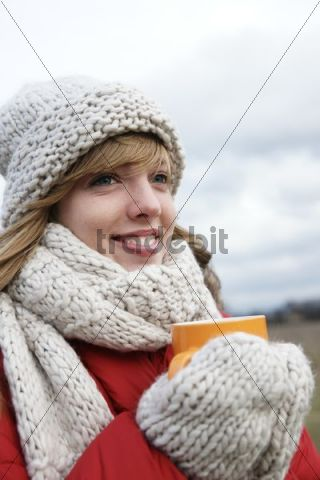 Girl wearing a scarf and a hat, holding a tea cup