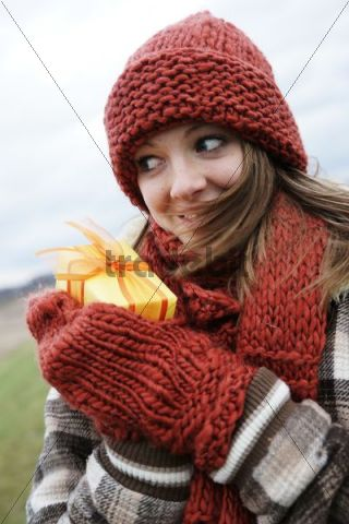 Laughing teenager wearing a hat and a scarf, holding a present