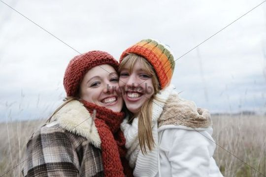 Two laughing teenage girls wearing hats and scarfs