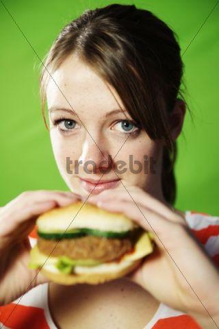 Female teenager holding a hamburger