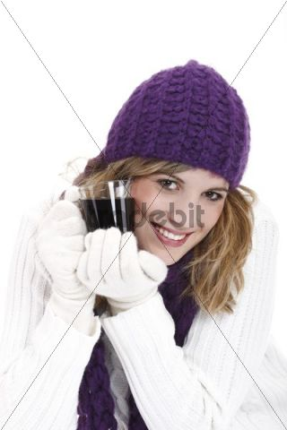 Young woman wearing a purple woolen cap and scarf drinking mulled wine, Gluehwein