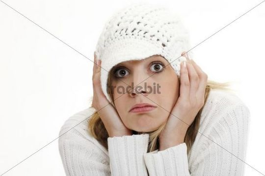 Young woman wearing a white knitted jumper and a woolen cap, looking astonished