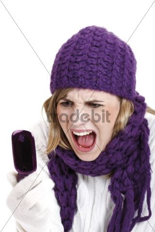 Young woman wearing a purple woolen cap and scarf screaming into a mobile telephone