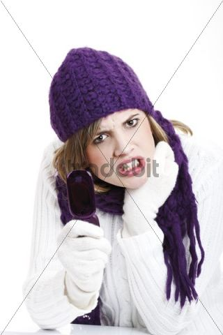 Young woman wearing a purple woolen cap and scarf holding a mobile telephone