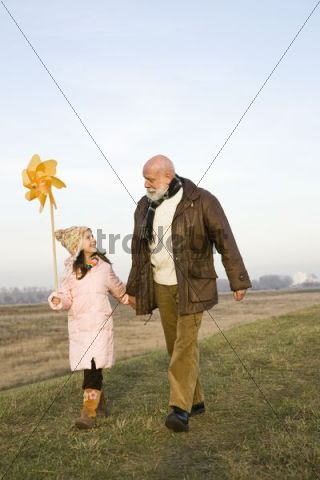 Girl with a pinwheel out for a walk with her grandfather