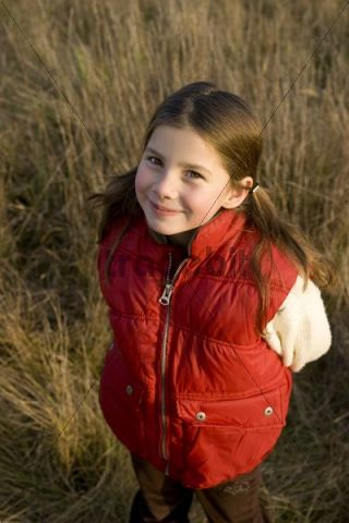 Smiling girl standing in a field