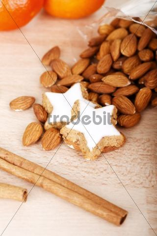 Cinnamon cookies with almonds, tangerines and cinnamon sticks on a wooden table