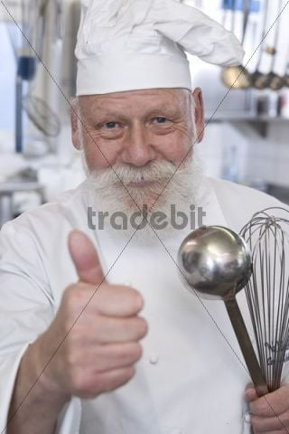Cook wearing a chefs hat, holding a soup ladle and an egg whisk