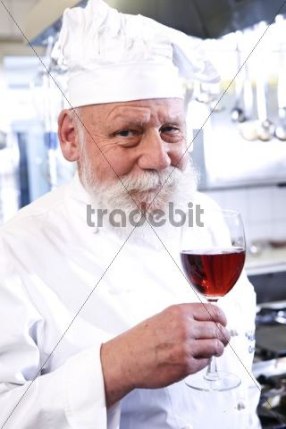 Cook wearing a chefs hat, smiling and holding a glass of red wine