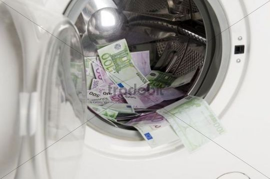 Euro banknotes in a washing machine, symbolic of money laundering