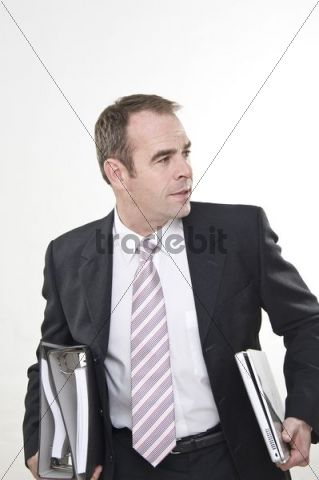 Businessman carrying document files and laptop