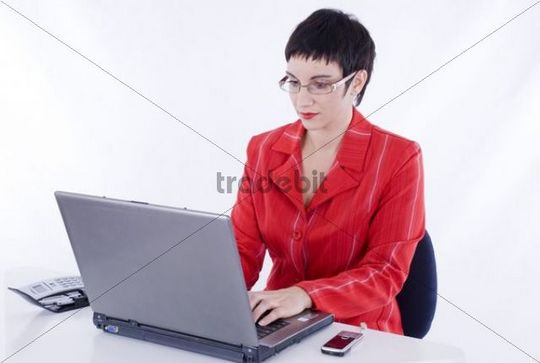 Businesswoman in an office, working on a laptop
