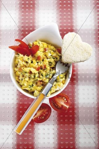 Scrambled eggs with tomatoes, chives and heart-shaped toast
