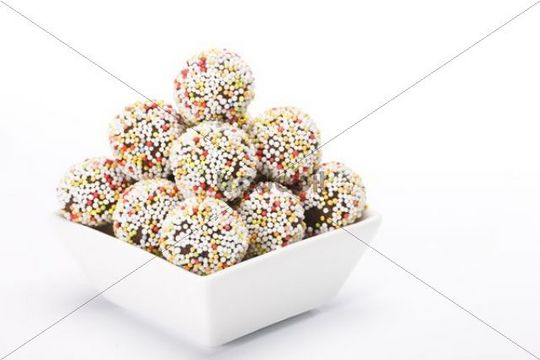 Rum truffles with coloured sugar sprinkles in white bowl