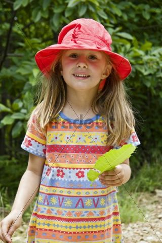 Young girl wearing a red sun hat
