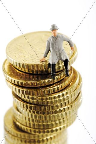 Figurine on a stack of coins, man wearing a raincoat